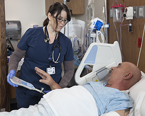 Healthcare provider caring for man in intensive care unit bed.